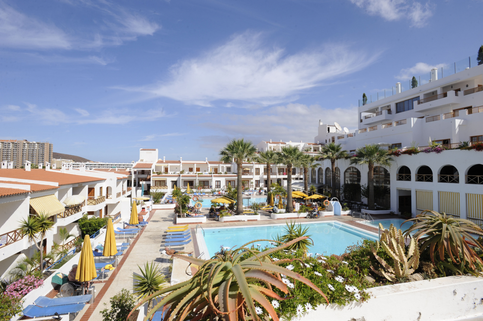Overlooking the courtyard of the Mar y Sol hotel. A number of sun loungers surround a swimming pool which is in the centre of the courtyard.