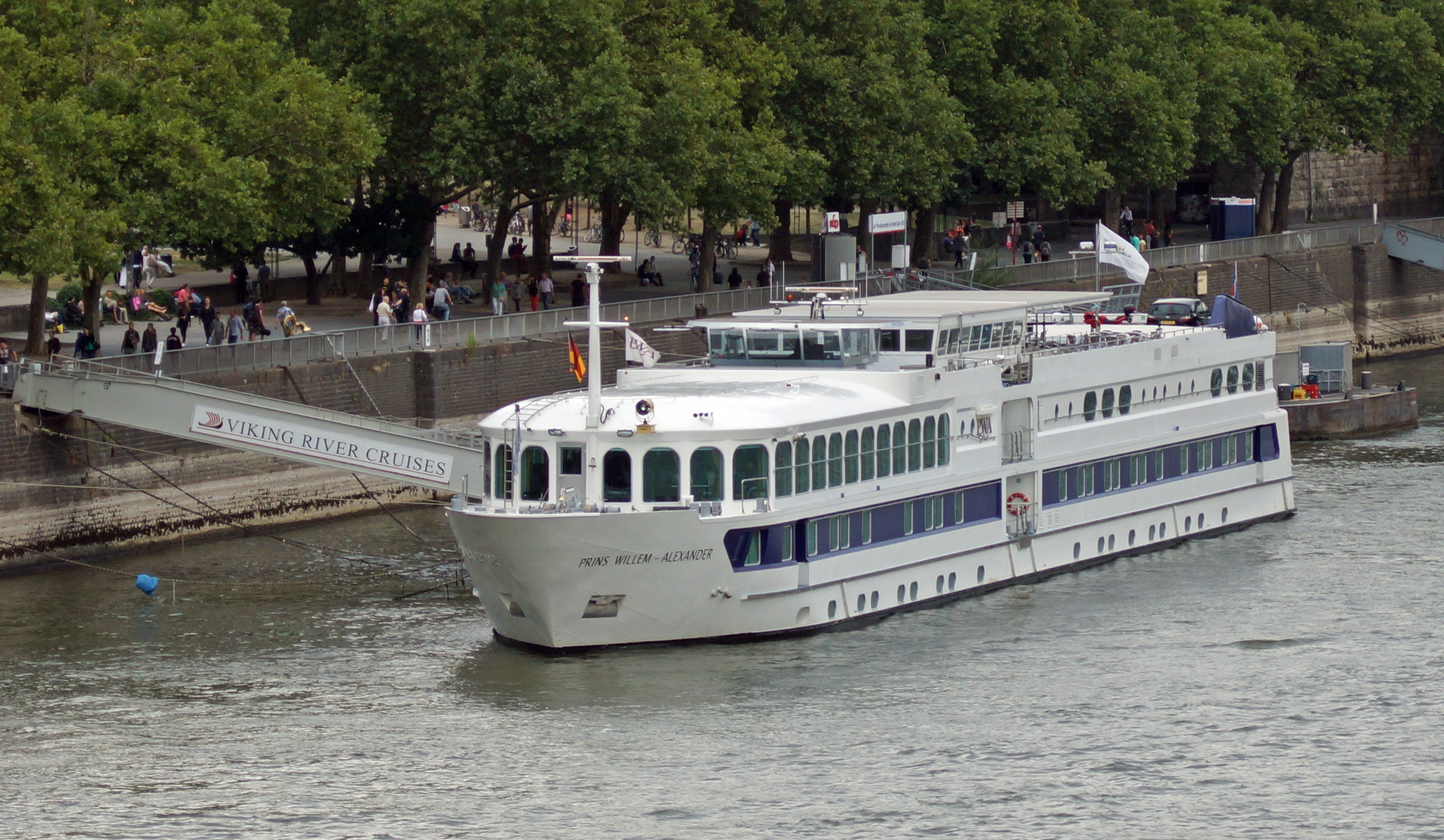 A long white cruise ship docked on the side of the river with a gangway leading to the riverbank