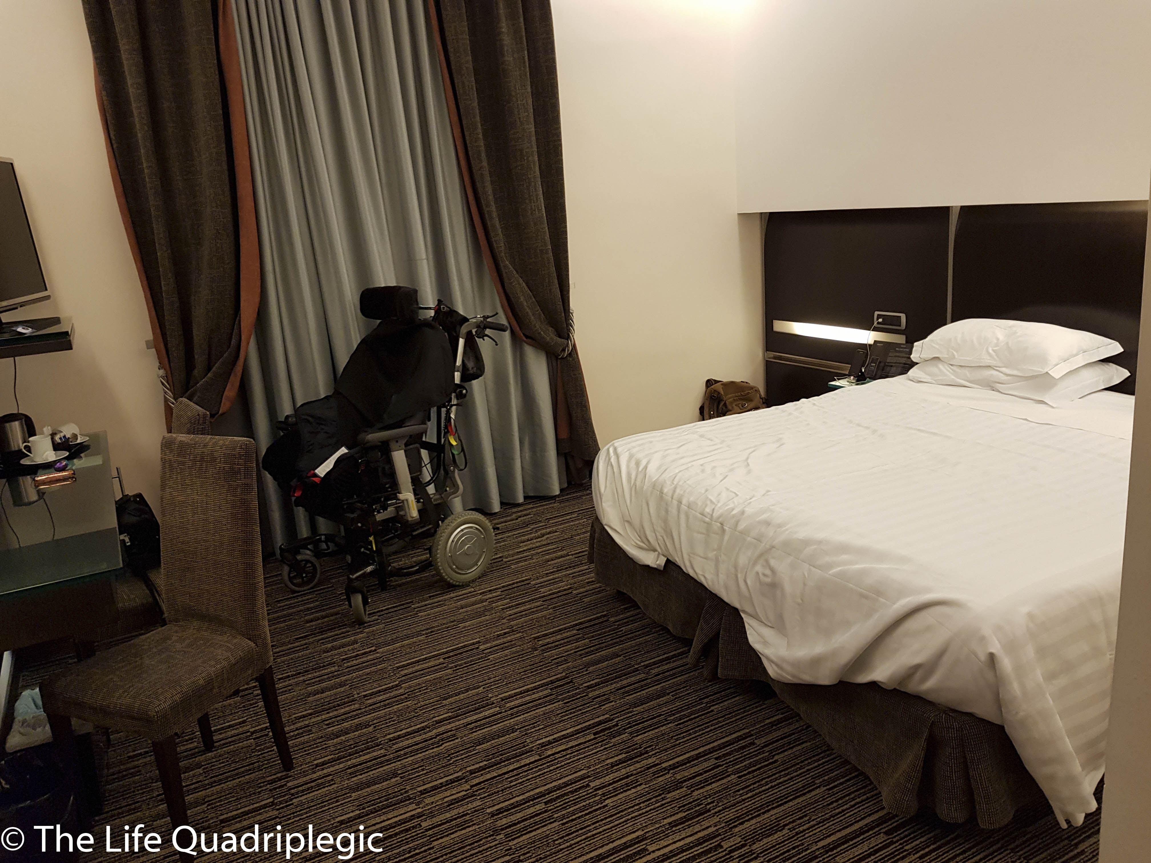 A hotel room with a double bed and a wheelchair next to the bed