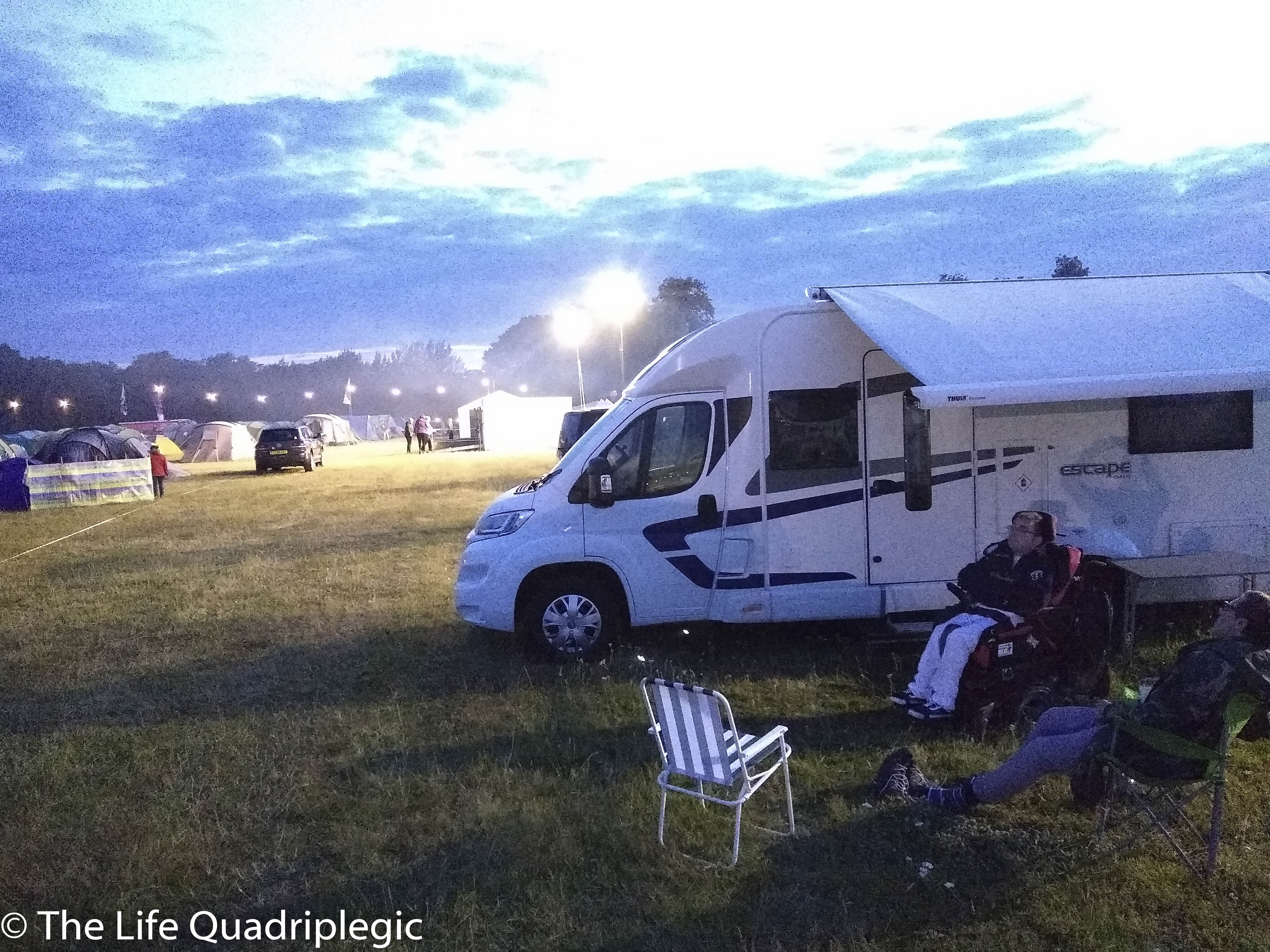 A side view of a motorhome with a young man in a powerchair sat next to it and another man in a camping chair