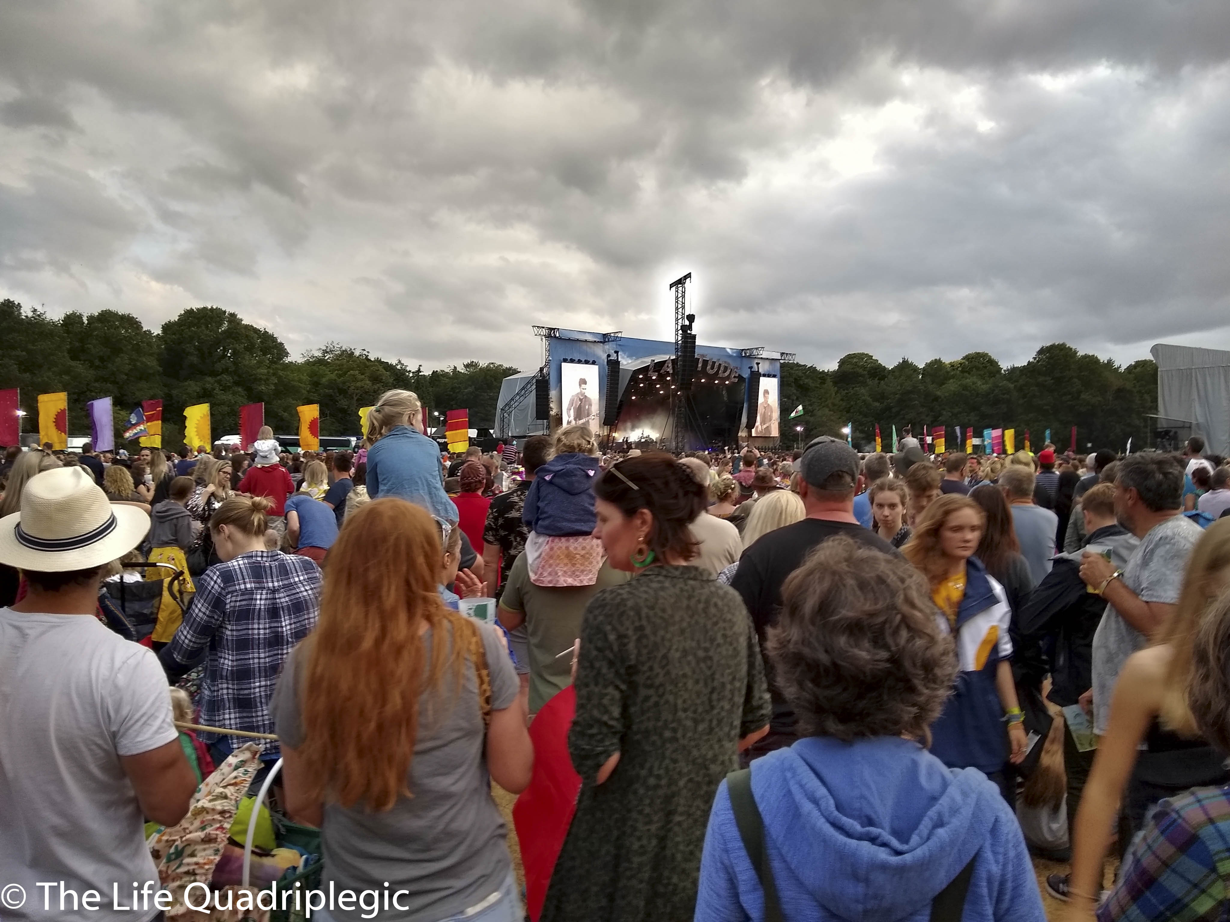 A large crowd is stood in the foreground looking towards a stage in the background under a cloudy sky.