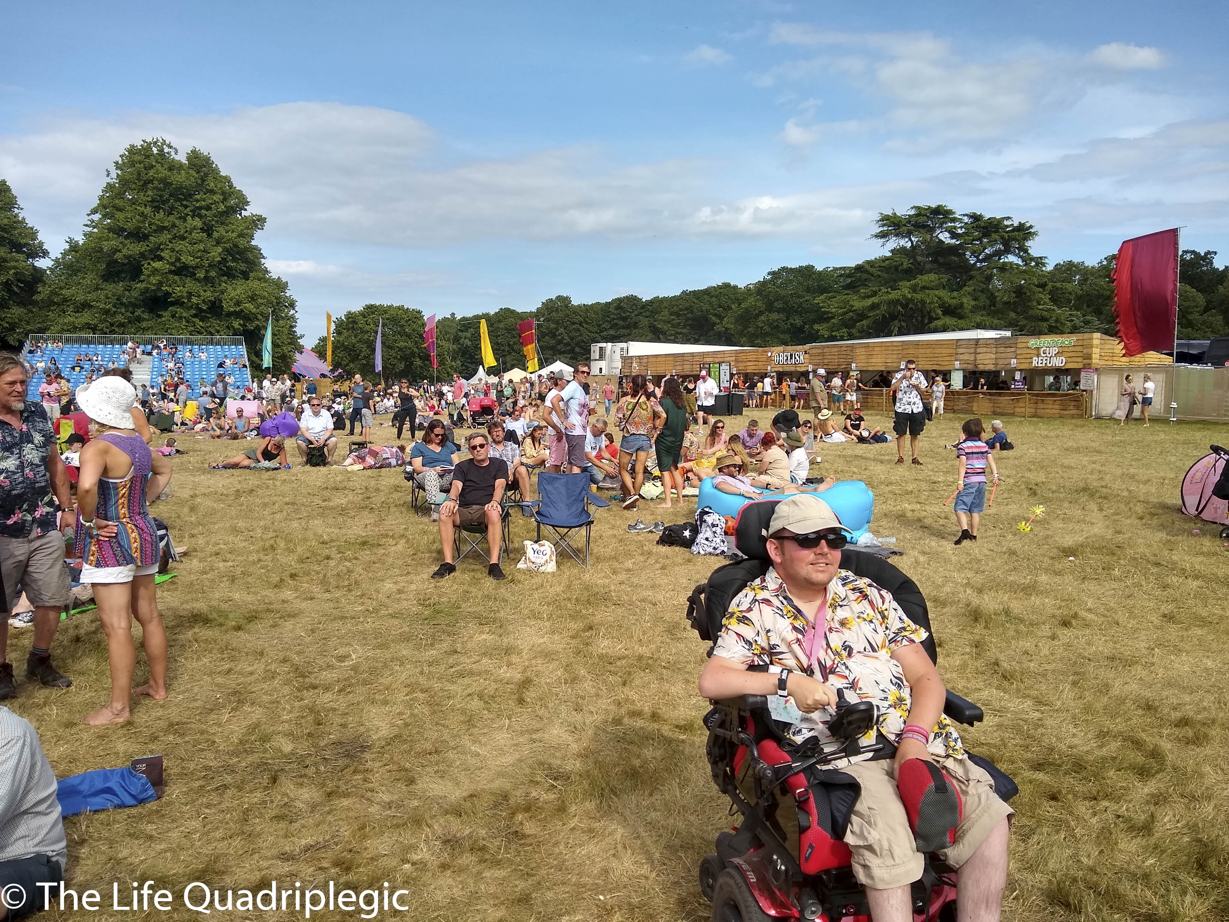 A young man in a powerchair Smiles at the camera while sat in a grassy field. Lots of other people are milling about.