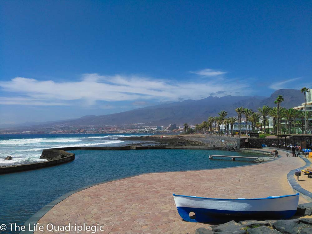 A small wooden boat rests on a paved area next to a tidal pool. Mountains in the background under some wispy clouds and the largely blue sky