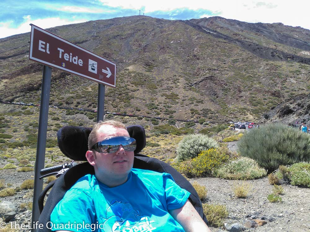 """A male wheelchair user smiles at the camera with a sign pointing to the mountain in the background which reads """"El Teide"""""""