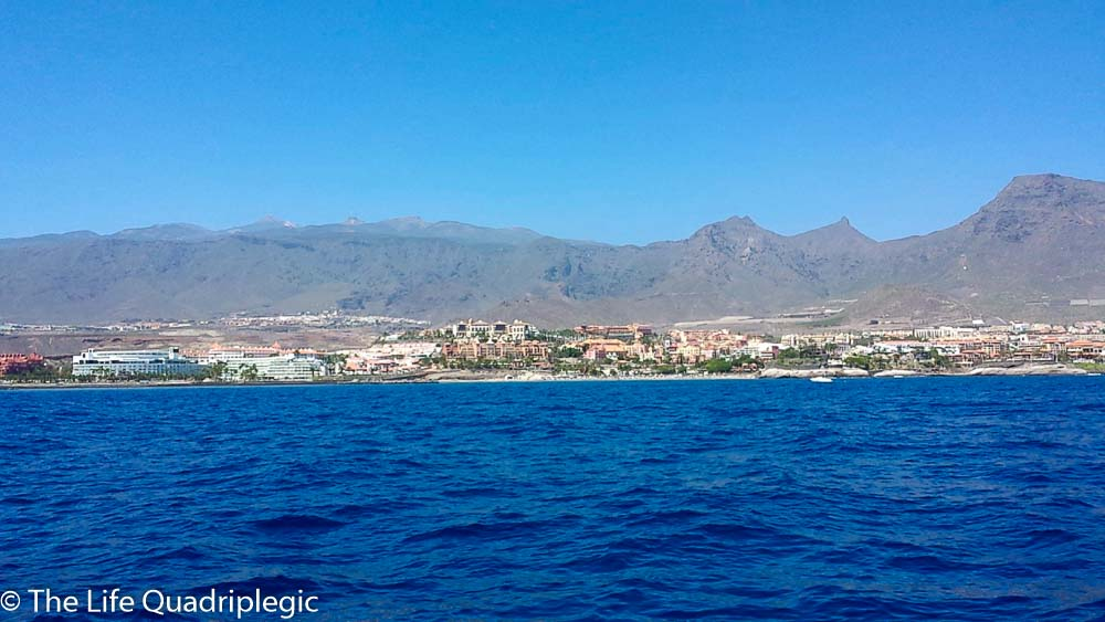 A clear blue sky at the top of the picture with mountains underneath. A town is on the coastline With the calm ocean in the foreground
