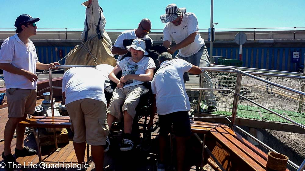 5 men are lifting a man in a wheelchair up some steps at the front of the boat onto the Harbourside