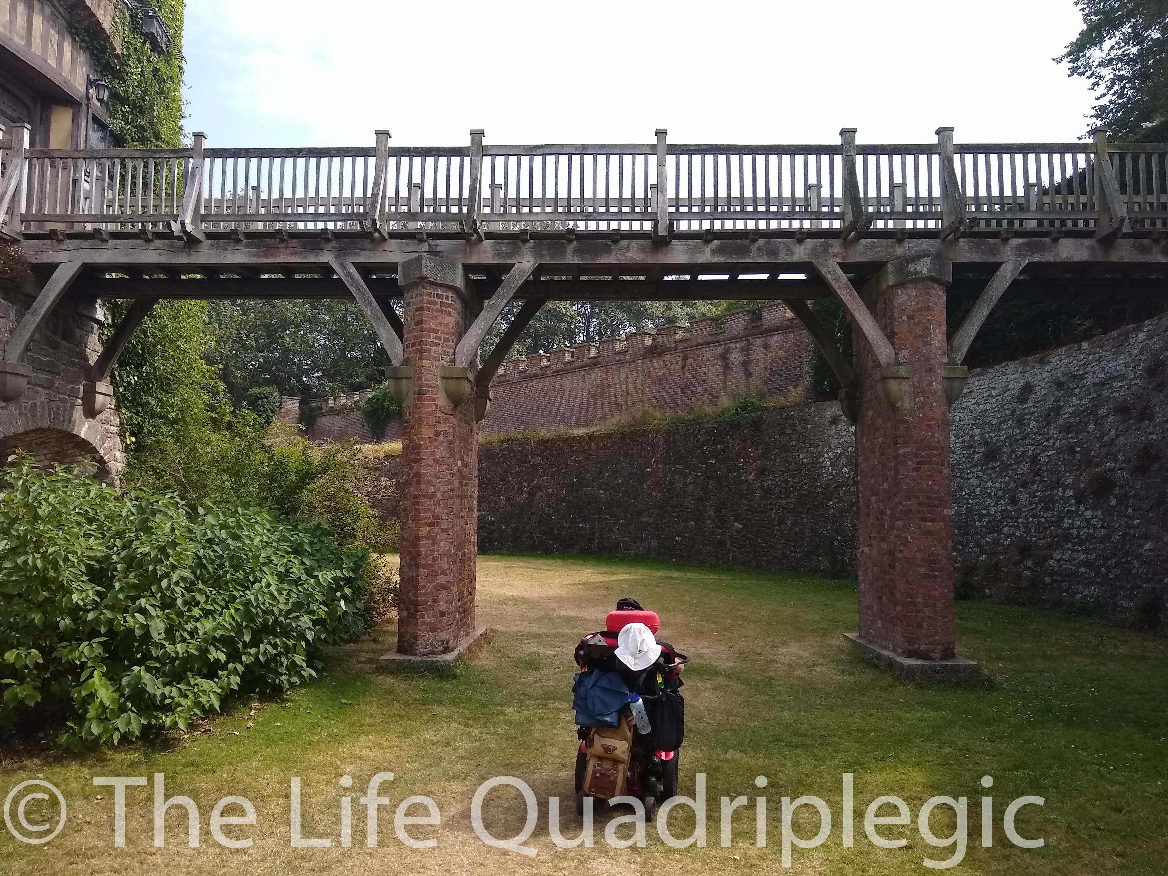 A Powerchair user sits on the grass in the castle moat with a bridge in front of him running from one side of the most to the other.
